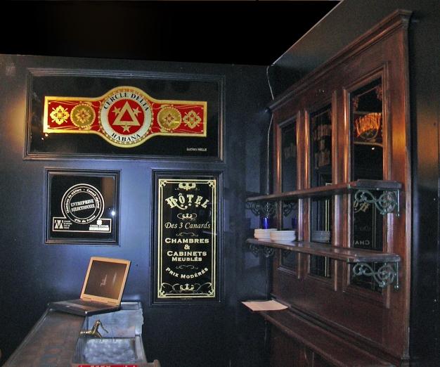 """Vue des étagères du comptoir de côté avec les panneaux Cercle Delta Habana, Hôtel des trois Canards et """"Entreprise sélectionnée"""""""