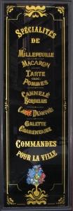 """Panneau décoratif """"Spécialités de millefeuille - Macaron - Tarte aux pommes - Cannelé bordelais - Carré dijonnais - Galette charentaise - Commandes pour la Ville"""""""